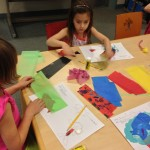Kindergarten students creating their tissue paper collages, in the style of Eric Carle.